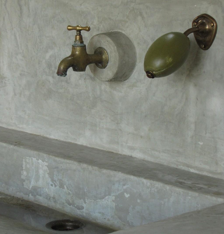 Savon de Marseille zeepbolhouder bij wasbak met koperen kraan in beton ciré